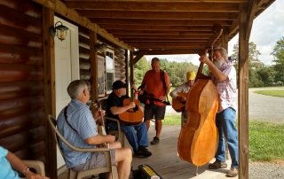 Guys playing music on the porch at Cool Breeze Campground