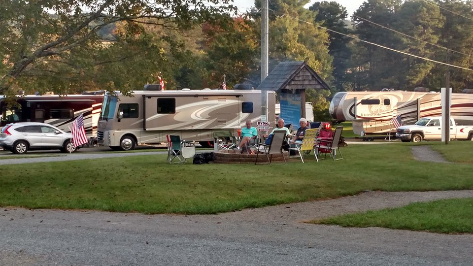 Small gathering of campers around the firepit